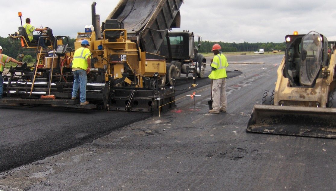 men workers with machines and dump truck repaving asphalt