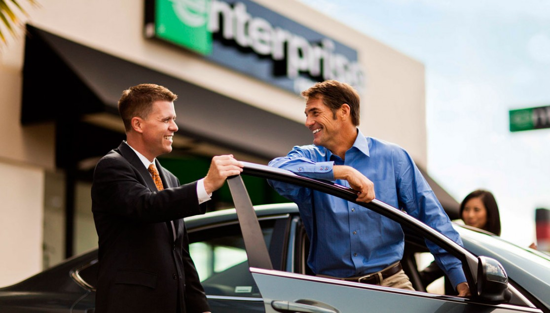 two men standing with rental car in front of building